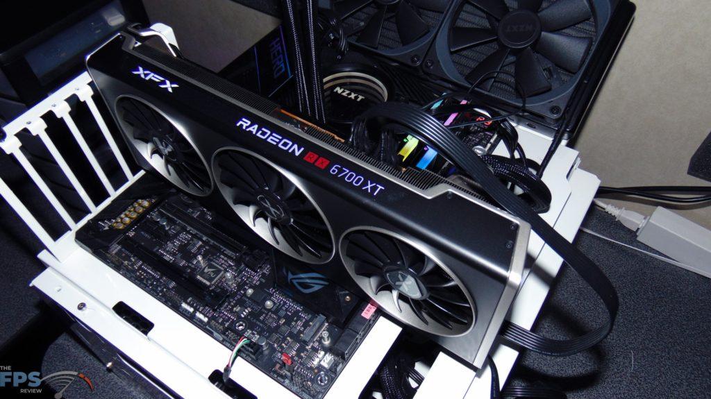 XFX SPEEDSTER MERC 319 BLACK AMD Radeon RX 6700 XT installed in motherboard on testing bench top view rgb lighting